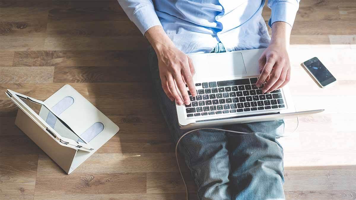 Mann mit Laptop, Tablet und Handy